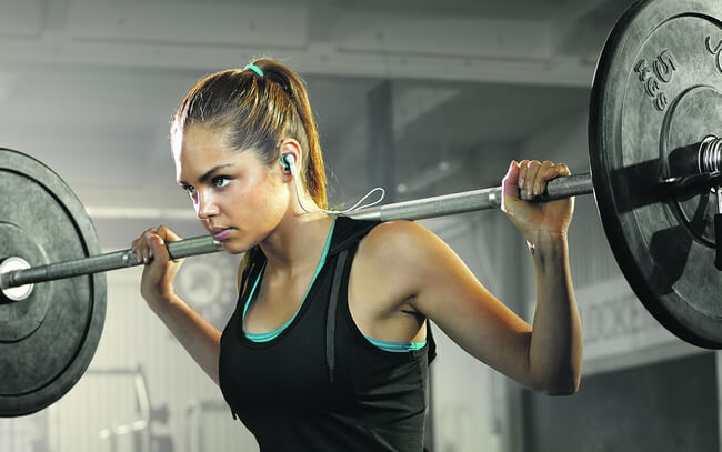 Woman lifting weights with Jabra Coach