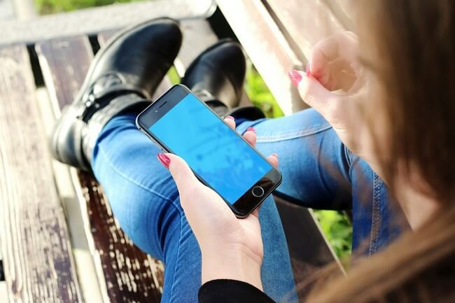 Woman wearing jeans holding an iPhone