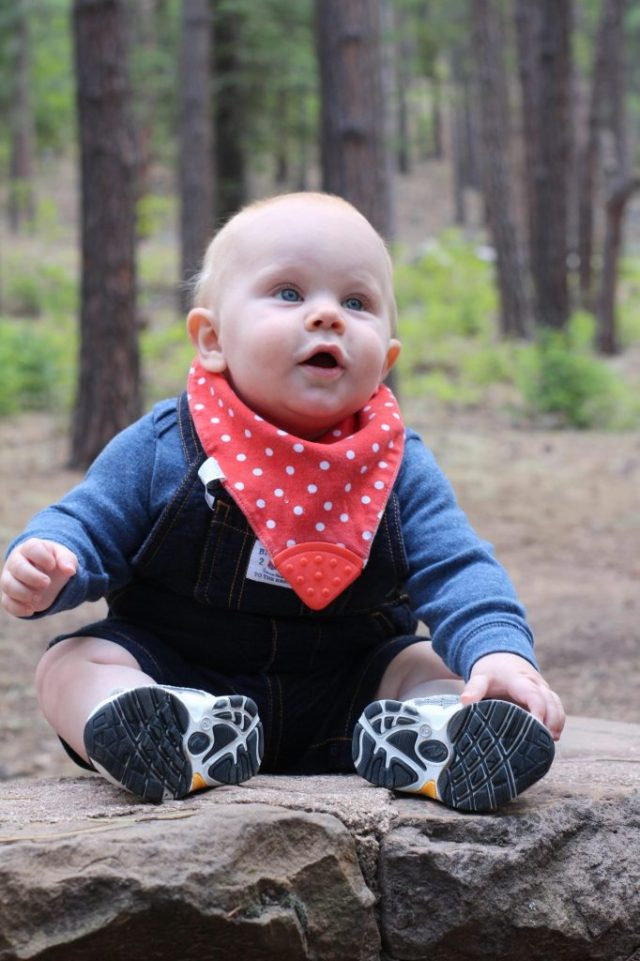 Happy baby sitting on the ground in a pine forest.
