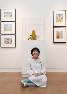 Eimi Takano sits in front of her plush sculpture, Ribbon Camp.