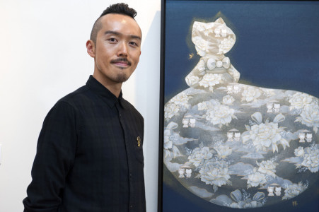 Martin Hsu stands next to his painting Hello Kitty Transcendence, on view now as part of Hello! Exploring the Supercute World of Hello Kitty at JANM.
