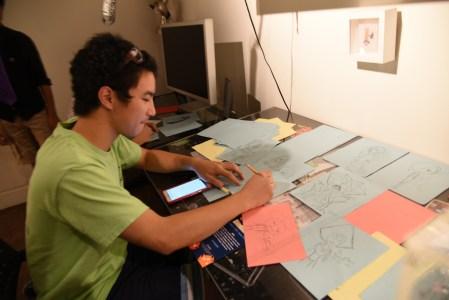 A guest tries his hand at drawing inside a replica of artist Edwin Ushiro's studio. Photo by Nobuyuki Okada.
