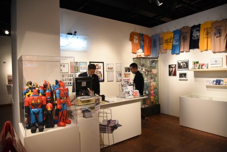 Curator Eric Nakamura, left, and artist Mike Lee check on a few last-minute details in the replica Giant Robot store. Photo by Nobuyuki Okada.