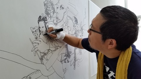 Katsuya Terada at work in the JANM galleries. Photo by Carol Cheh.