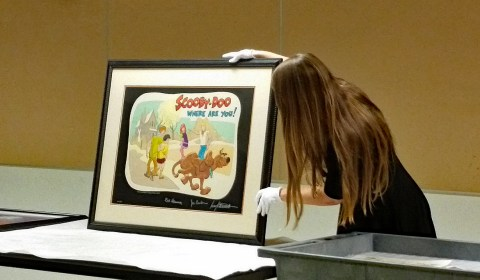 JANM Collections Manager Maggie Wetherbee holds up a limited edition Scooby-Doo print signed by Iwao Takamoto, Joe Barbera, and Bill Hanna.