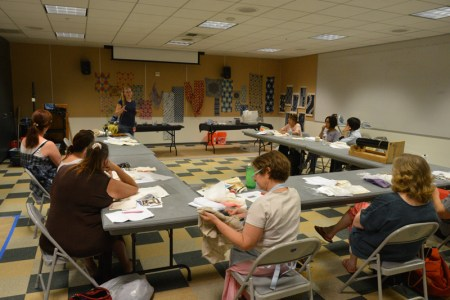Glennis Dolce leads a shibori class at JANM, flanked by samples of resist cloth dyeing. Photo by Tokumasa Shoji.