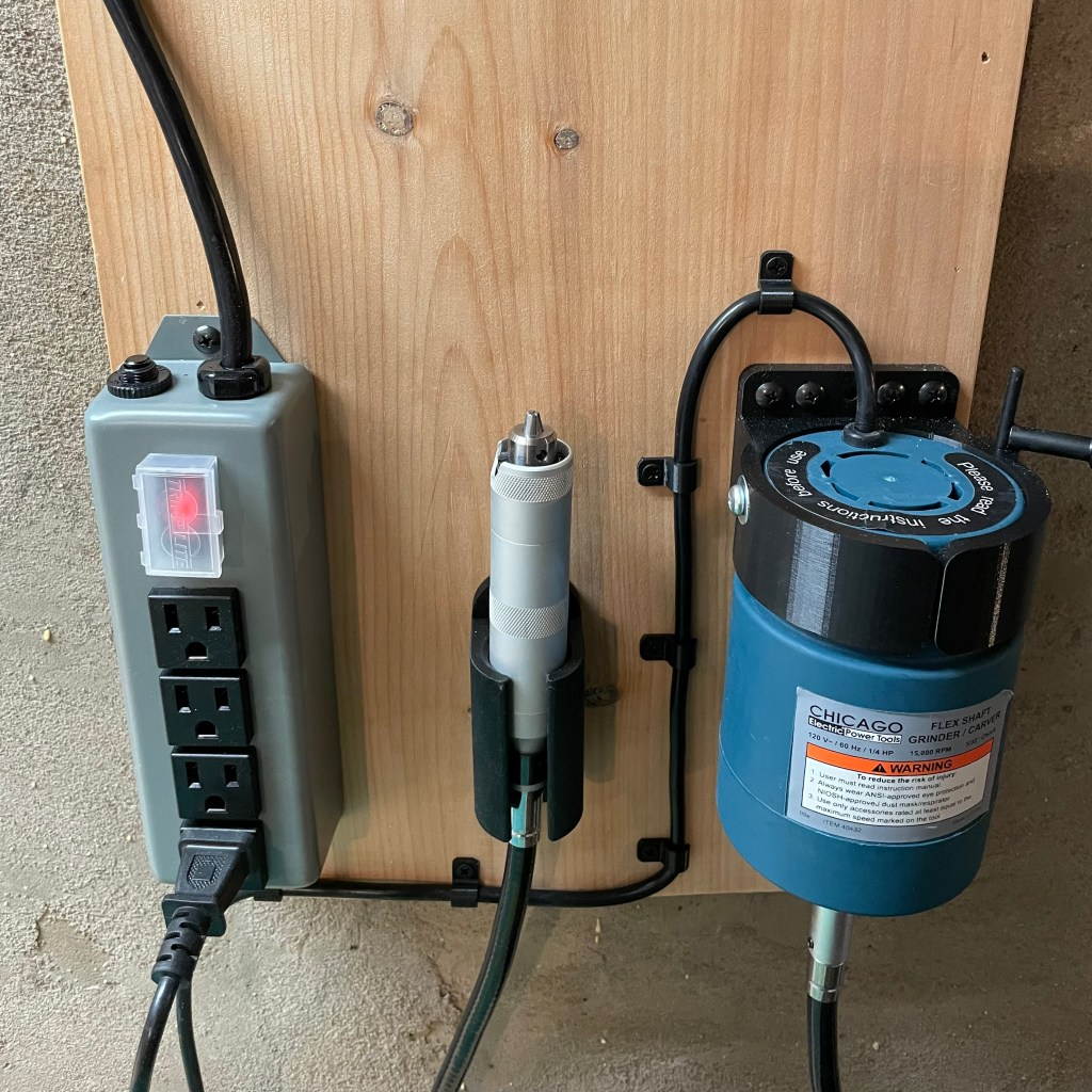 Image of grinder, hand piece and power strip mounted on the wall.