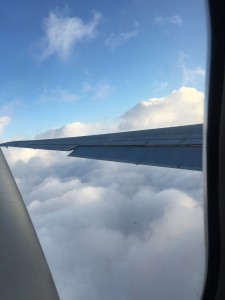 Looking out the plane window above the cloud line.