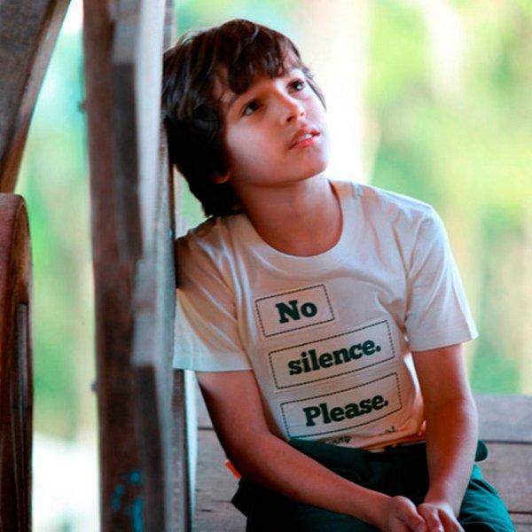 """Escola de idiomas - Garoto apoiado na parede com uma camiseta escrito """"No silence. Please""""."""