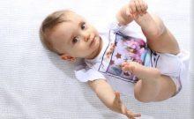 desmame - bebê menina deitada de barriga para cima, segurando um dos pés