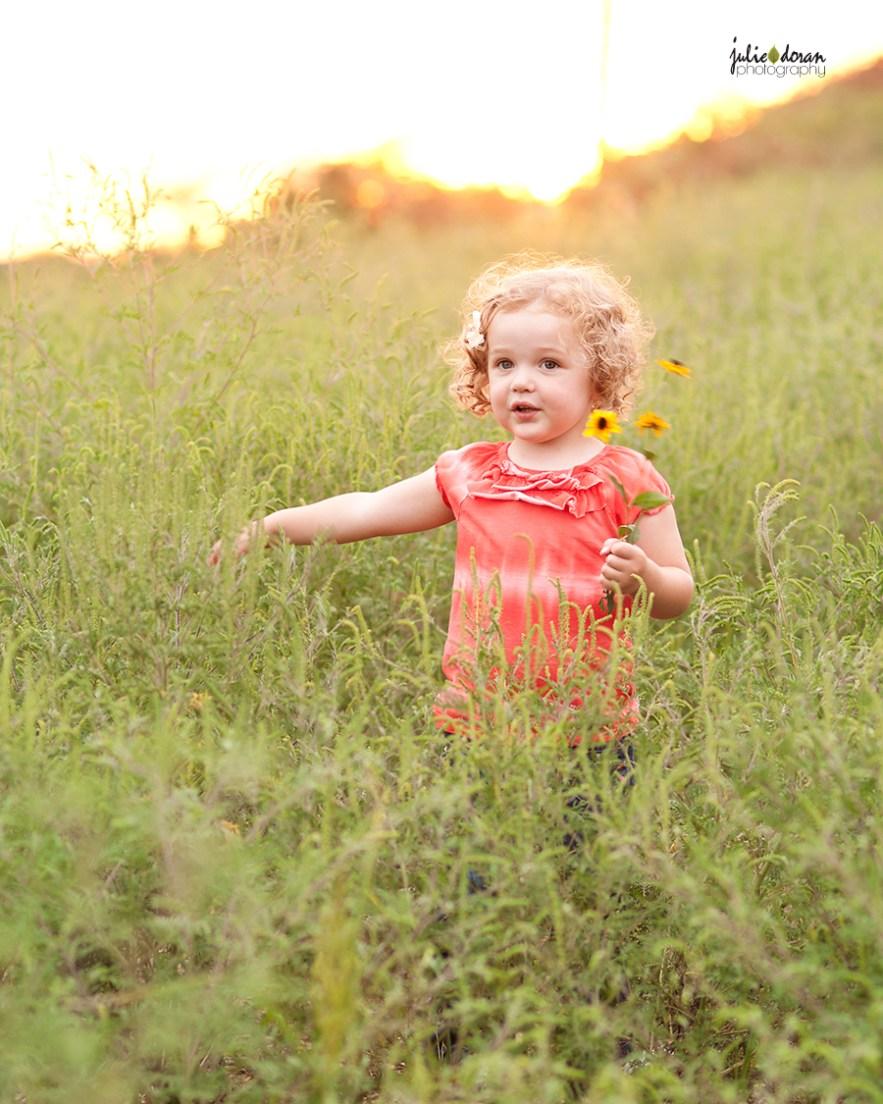 curly haired girl walking in flower field
