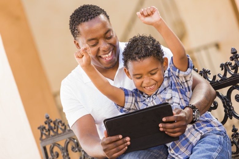 A man and his son looking at a tablet with excitement.