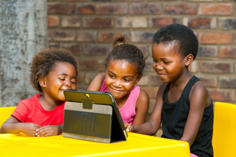 Three kids staring at a tablet