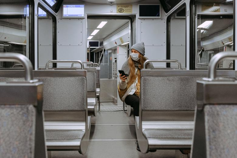 A woman wearing a face mask in a train