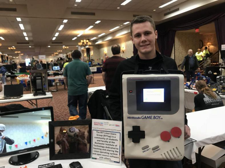 Taylor Bowling stands next to the Spy Pi, a discreet picture frame that takes a picture when it detects movement at the Rochester Mini Maker Faire 2017