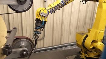 Robotic arm precision grinding a gun barrel