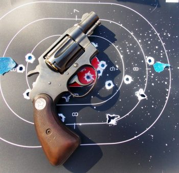Revolver atop a target with multiple bullet holes