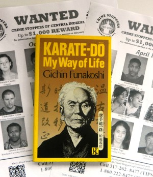 Wanted posters with a book by Gichin Funakoshi