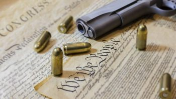 Constitution with bullets and a handgun
