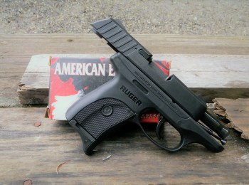 Ruger EC9s with slide locked back resting against a box of American Eagle ammunition