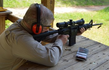 Bob Campbell firing a scoped AR-15 from a benchrest position for rifle marksmanship