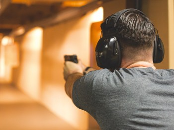 Rearview of man shooting a pistol at an indoor range