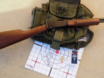 Henry Pump Octagon rifle over an olive drab colored pouch and paper targets