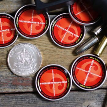 Firebird targets with silver dollar and loose rounds of ammunition