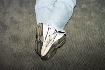 man's feet crossed while laying face down