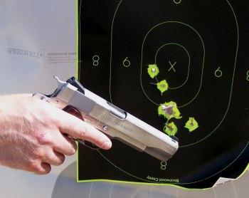 Handgun with bullet holes in the target