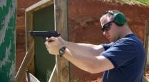 Man firing a pistol from a braced position
