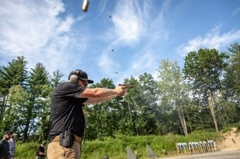 Shooting a 9mm pistol with four cartridge cases in the air