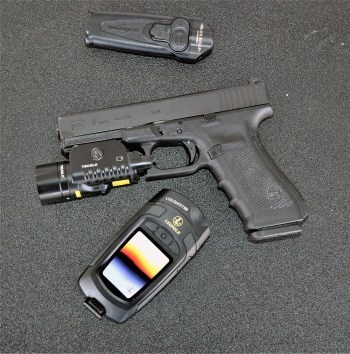Glock handgun with a TruGlo light, pocket knife, and thermal imaging unit