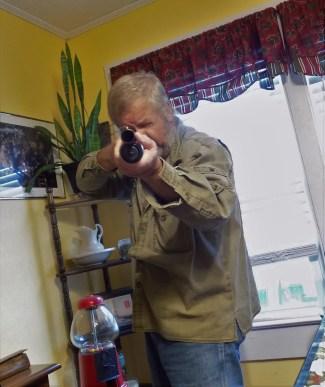Bob Campbell in a defensive position aiming a shotgun