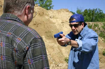 Man being robbed at gun point initiating his survival instinct