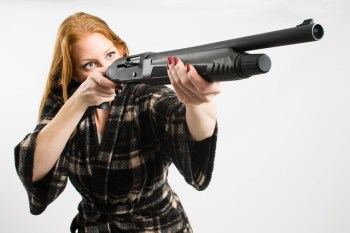 Woman in a robe aiming a shotgun in a home defense situation