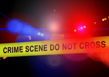 Red and blue police lights behind yellow crime scene tape