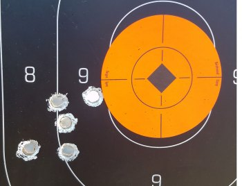 Silhouette target with orange center showing bullet hole grouping