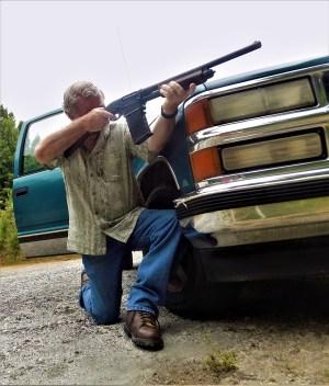 Bob Campbell shooting the Remington 870 DM shotgun while kneeling behind a car