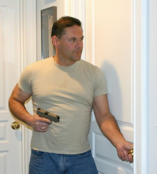 Man holding a pistol while opening a door.