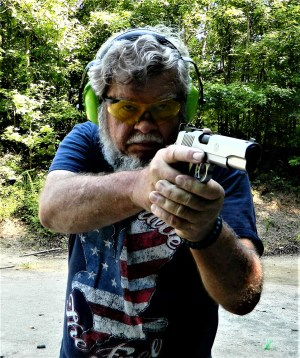 Bob Campbell shooting a 1911 10mm pistol with a two-handed grip