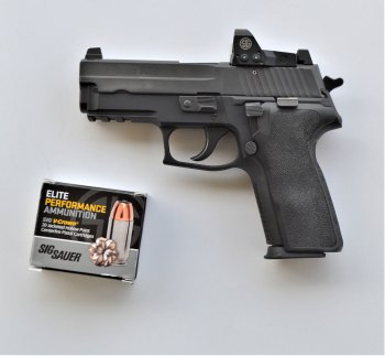 SIG Sauer P229 pistol left profile with one box of SIG ammunition