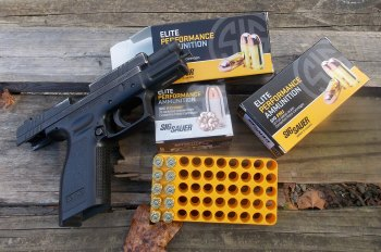 SIG Sauer handgun with slide locked back and two boxes of SIG Elite ammunition