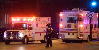 Two ambulances with lights on behind crime scene tape with armed good guys