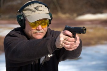 Man wearing safety glasses and hearing protection shooting a 1911 pistol with a two handed grip