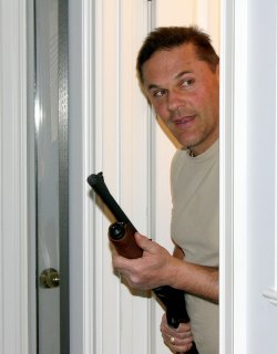 Man peeking through a doorway holding a shotgun