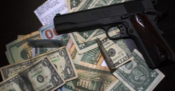 black handgun on top of a pile of paper money to protest gun control efforts of lobbyists