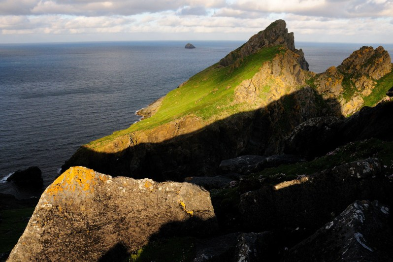 Pyramidal shaped small island with grassy slopes and yellow lichen, bathed in evening sunshine, surrounded by a blue sea