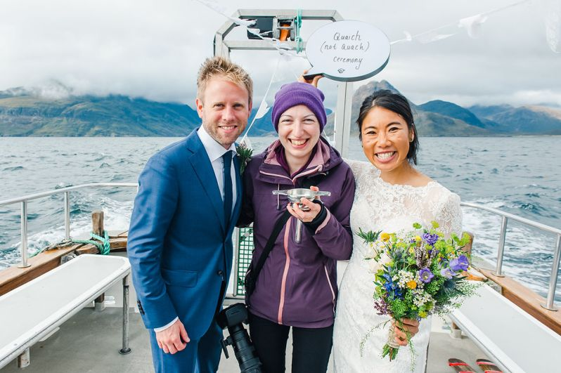 Photographer and blogger Karen Thorburn standing between a bride and groom on a boat on a loch with mountains in the distance