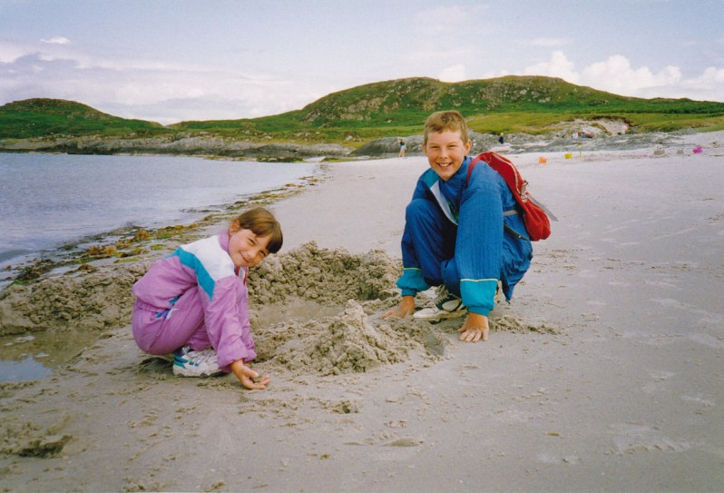 Two young children dressed in shell suits and smiling while digging on a sandy beach with low green hills in the distance